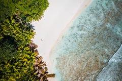 O banho de sol da menina em cocos tropicais encalha com rochas, as palmeiras e as ondas de oceano bonitas Tiro a?reo do zang?o se imagens de stock royalty free