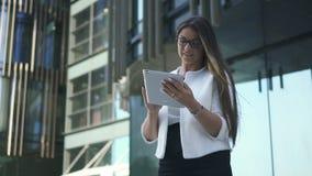 O banqueiro de mulher principal à moda bonito está usando a tabuleta que está no fundo urbano da construção vídeos de arquivo