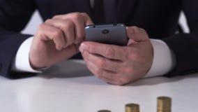 O banqueiro masculino que trabalha no smartphone com moeda empilha a tabela, verificando a taxa de moeda vídeos de arquivo