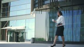 O banqueiro principal seguro da mulher de negócios está bebendo o café, andando no fundo do prédio de escritórios vídeos de arquivo