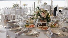 O banquete com as grandes mesas redondas com toalhas de mesa brancas classificou pratos deliciosos, arranjos de flor e decoração  video estoque