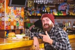 O bar est? relaxando o lugar para ter a bebida e relaxar O homem com cerveja da bebida da barba come o menu do hamburguer Aprecie foto de stock royalty free