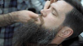 O barbeiro barbeia homens com uma barba longa com a lâmina de lâmina reta no cabeleireiro ou no barbeiro de s Corte de cabelo e r filme