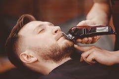 O barbeiro corta sua barba para equipar na poltrona foto de stock