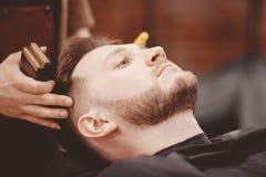 O barbeiro corta sua barba para equipar na poltrona imagens de stock royalty free