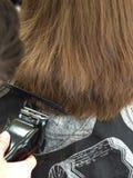 O barbeiro corta uma mulher por uma tosquiadeira do barbeiro imagem de stock