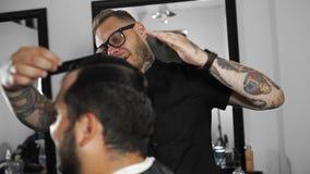 O barbeiro de Tattoed faz o cabelo que denomina com o gel de cabelo para o cliente após o corte de cabelo na barbearia, o corte d vídeos de arquivo