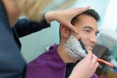 O barbeiro do homem barbeia a barba dos clientes foto de stock