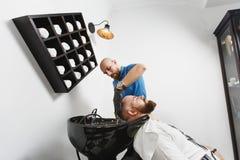 O barbeiro do homem serve o cliente no salão de beleza imagens de stock royalty free