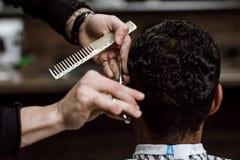 O barbeiro está cortando o cabelo de um homem que guarda tesouras e está penteando-o em suas mãos oposto ao espelho em um barbeir fotografia de stock royalty free