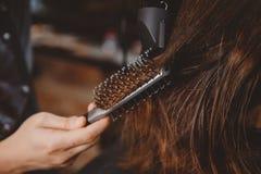 O barbeiro faz o cabelo que denomina para equipar com hairdryer e pente imagens de stock royalty free