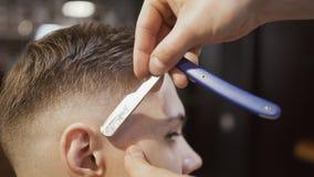 O barbeiro faz o contorno ao penteado com lâmina afiada filme