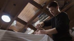 O barbeiro faz o contorno do penteado ao homem novo video estoque