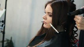 O barbeiro faz a denominação de uma menina com cabelo encaracolado Bar da beleza do estilista Mulher em um salão de beleza de bel filme