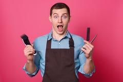 O barbeiro masculino chocado guarda o equipamento necessário para fazer o penteado, mantém a maxila deixada cair, olhares fixos n foto de stock royalty free