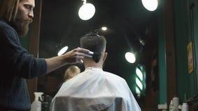 O barbeiro masculino faz um corte de cabelo para o cliente farpado e a utilização de um talco no barbeiro vídeos de arquivo