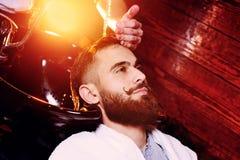 O barbeiro ou o cabeleireiro lavam a cabeça do cliente Foto de Stock