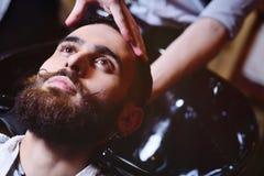 O barbeiro ou o cabeleireiro lavam a cabeça do cliente Fotos de Stock Royalty Free