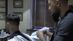 O barbeiro põe a toalha sobre o cliente video estoque