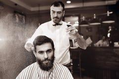 O barbeiro polvilha no cabelo de um cliente masculino novo de uma barbearia com água de um bulbo Imagem de Stock Royalty Free