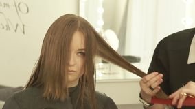 O barbeiro que penteia e que corta o cabelo da mulher com cabeleireiro scissors no estúdio da beleza Feche acima da fatura do bar video estoque