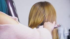 O barbeiro seca com secador de cabelo e cabelo dos pentes filme