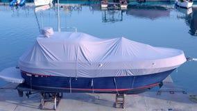 O barco coberto com o encerado branco no porto é estacionado no cais video estoque