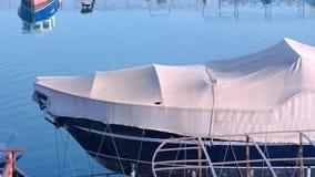 O barco coberto com o encerado no porto é estacionado na água video estoque