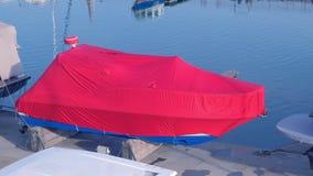 O barco coberto com o encerado vermelho no porto é estacionado no cais video estoque