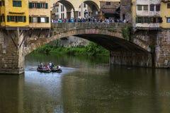 O barco com os povos perto da ponte no rio fotografia de stock