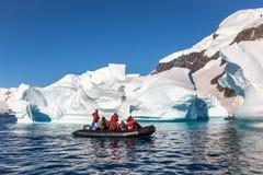 O barco completamente dos turistas explora os iceberg enormes que derivam na baía imagens de stock royalty free