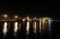 O barco de carga inteiramente carregado do transporte descarregou na noite imagem de stock