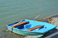 O barco de madeira velho para a água anda na costa pebbled de um lago da montanha Fotografia de Stock