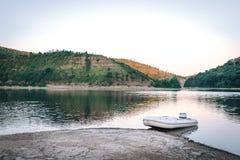 O barco de motor branco pequeno no rio da montanha, por do sol, pescando o conceito imagem de stock