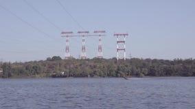O barco de motor flutua no rio na perspectiva das torres de alta tensão da transmissão de energia filme