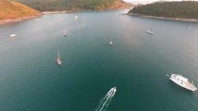 O barco de motor inflável vai ao iate perto das ilhas tropicais Tiro slowmotion aéreo do tempo do por do sol de HD tailândia video estoque