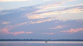 O barco de motor move-se rapidamente no lago ou no rio no alvorecer video estoque