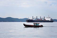 O barco de passageiro pequeno que corre no mar e tem o navio de carga Fotografia de Stock