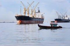 O barco de passageiro pequeno que corre no mar e tem o navio de carga Imagem de Stock Royalty Free