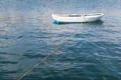 O barco de pesca de madeira branco flutua na água imóvel Fotos de Stock