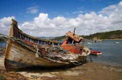 O barco de pesca destruiu em um banco de rio rochoso Imagens de Stock Royalty Free