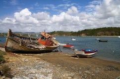 O barco de pesca destruiu em uma costa rochosa Imagens de Stock