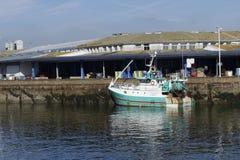O barco de pesca do branco e da turquesa entrou ao lado do cais com fundo do armazém Fotografia de Stock Royalty Free