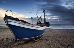 O barco de pesca na praia ajardina com céu tormentoso Fotografia de Stock Royalty Free