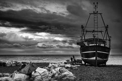 O barco de pesca na praia ajardina com o céu tormentoso preto e branco Foto de Stock