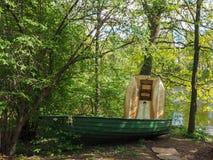O barco de pesca verde velho está na terra, estando por uma árvore na floresta no banco de rio imagens de stock