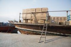 O barco do dhow de Dubai Creek amarrou aproximadamente para descarregar bens diferentes no cais, Emiratos Árabes Unidos Fotos de Stock Royalty Free