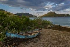 O barco do pescador idoso na praia tropical Fotos de Stock