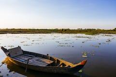 O barco do pescador no lago da exploração agrícola dos lótus em Camboja no por do sol Foto de Stock Royalty Free