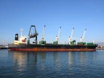 O barco do transporte é descarregado por guindastes no porto de Oakland em um clea Fotografia de Stock Royalty Free